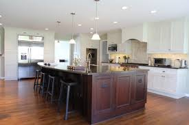 lighting two tone kitchen cabinets with large island and bar