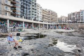 malta s walls are covered in murals and street art is covered in a man relaxed last week near a mural under an overhanging footpath along the coast in sliema malta credit gianni cipriano for the new york times