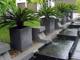 pond with gray concrete water fountain combined with green plants