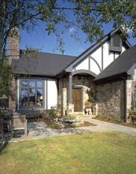 tudor home painted white with gray accents wood shingled roof