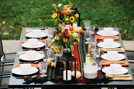 dining table arrangement flower vases with crockery arranged on dining table in backyard