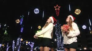 wonderful lovely twin sisters holding hands dancing with christmas