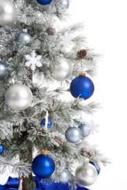 snow covered tree with blue and silver ornaments and white snow