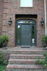 black door with camel trim and red brick house for the home