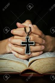 closeup of praying pose on bible while holding a cross stock
