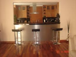 silver steel bar table with black top ad black stool on brown