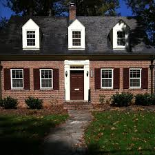 house with navy blue shutters on dark siding with brick exterior