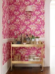 pink dining room features walls clad in pink floral wallpaper