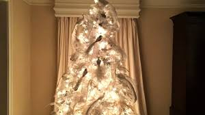 the finished winter wonderland of a white flocked christmas tree