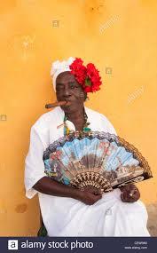 smoke fan for cigars cuban woman wearing a santeria white dress smoking a big cigar stock