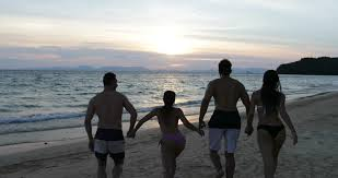 group of people on beach at sunset running in sea making splashes