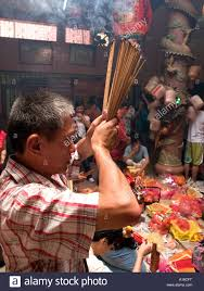 thanksgiving at a male devotee prays with joss in thanksgiving at the nan thien
