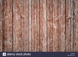 old gray wooden wall with damaged red paint layer background