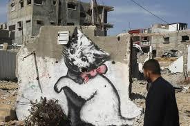 internet cats banksy kitten highlights gaza s plight nbc news image palestinians walk past a mural of a kitten presumably painted by british street
