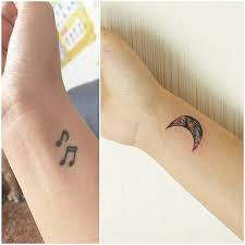 wrist tattoo of a watercolor style moon tattoo covering