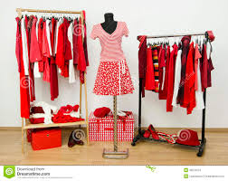 dressing closet with red and white clothes arranged on hangers and