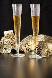pouring chagne in two glasses with festive gold