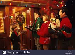christmas carolers christmas carolers at door nwreath candle warmth smile stock