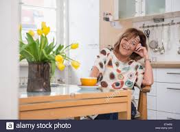 happy senior woman having tea at a dining table in kitchen munich