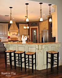 elegant four hanging kitchen lamps over rounded counter island as