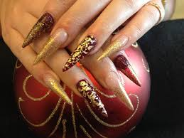 stiletto nails with gold glitter and gold foil over deep red gel