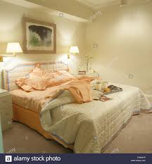 lighted wall lamps above bed with peach linen and a cream quilt in