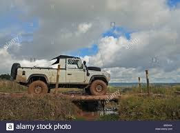 land rover wooden white 1990s land rover defender 110 with a top crossing a