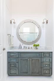 faded teal vanity cabinets and round silver mirror for a nautical