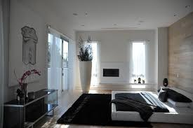 modern master bedroom with hardwood floors cement fireplace in
