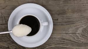 top of coffee cup hand putting spoon sugar into a cup of coffee and stirring it top