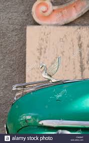 detail of metal swan ornament on classic green car at