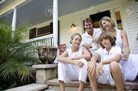 family sitting together on front porch steps stock photo picture