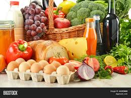 groceries in wicker basket including vegetables and fruits stock