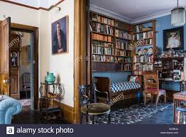 wooden bookshelves above antique daybed in study of nottinghill