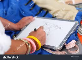 female fashion designer hands holding drawing stock photo