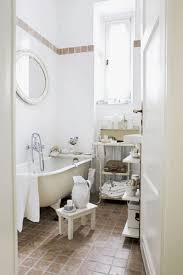 simple small bathroom with white tub white wall tiles and brownn