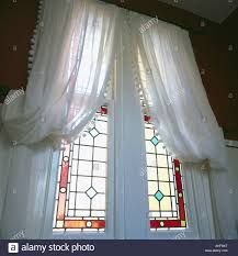 white voile curtains at tall stained glass windows stock photo