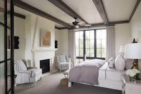 dark wood exposed beam master bedroom ceiling with a ceiling fan