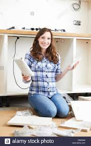 woman with self assembly furniture in kitchen stock photo royalty