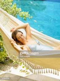 woman relaxing in a hammock by a pool stock photo getty images