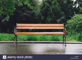 empty bench outside in the park after a rain with raindrops