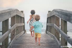 boy and running on wooden deck on the beach