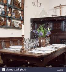 oak panelled wall in traditional dining room with oak settle and