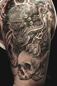 black ink foo dog with skull tattoo on man left half sleeve