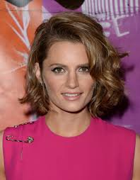 short mid hair pushed behind ears 15 of the best hairstyles for medium length curly hair beautyeditor