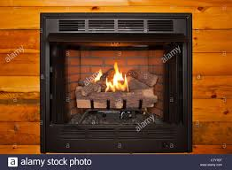 lit electric fireplace built into log cabin wall stock photo