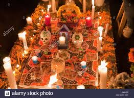 grave decorated with candles skulls food and flowers in