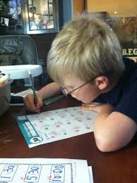 working on a math worksheet from kumon homeschooling is our