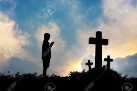silhouette of boy praying to a cross with heavenly cloudscape