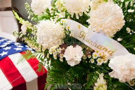 funeral spray stock photo of funeral spray of white flowers with husband banner